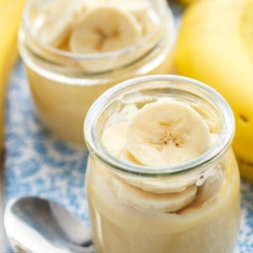 Two glasses of banana pudding with a spoon.