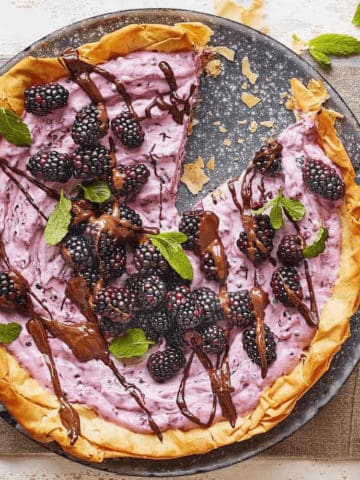 A blackberry tart on a dish with one piece of it already eaten.