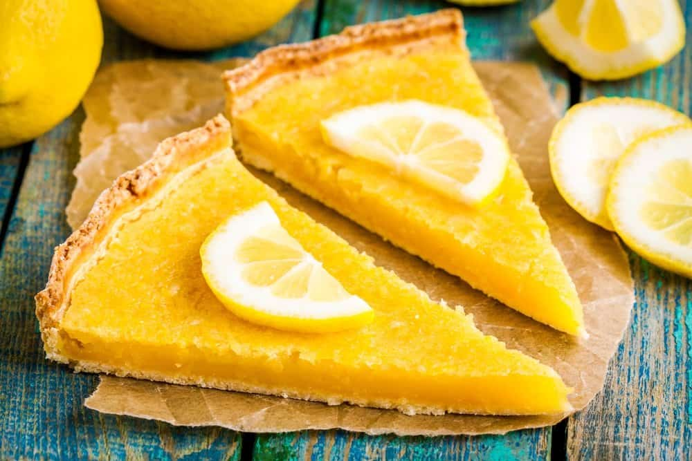 Two pieces of lemon tart with a slice of lemons on the top.