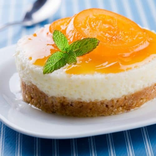 A peach cheesecake bite on a white plate with a spoon next to it.