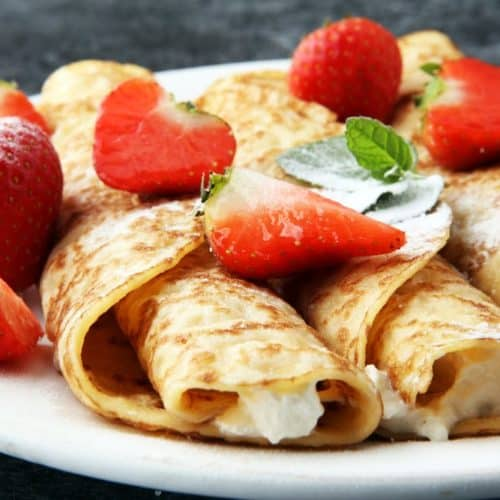 Three strawberry creamy crepes on a white plate with strawberries on top.