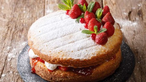 A strawberry sponge cake on a table.