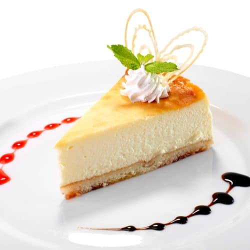 A piece of white chocolate cheesecake on a white plate with whipped cream on the top.
