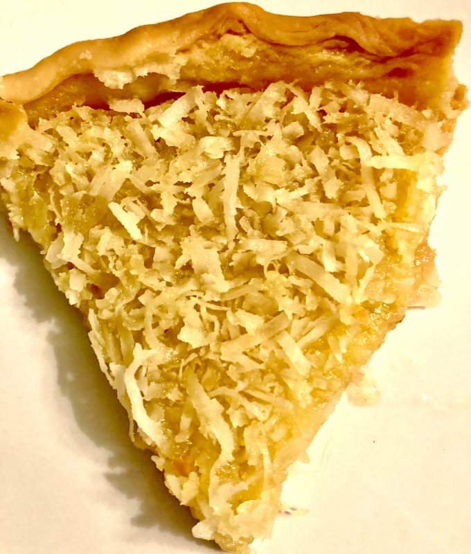 A slice of French coconut pie on a white plate.