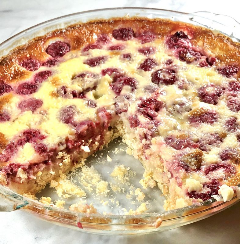 A close up of German raspberry custard kuchen with a slice missing.