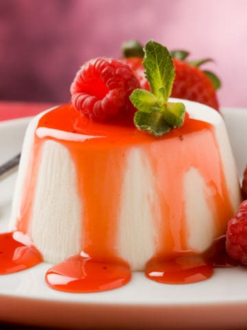 Panna cotta dessert recipe on a plate with strawberries.