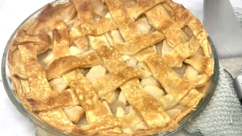 A full homemade apple pie on the table.