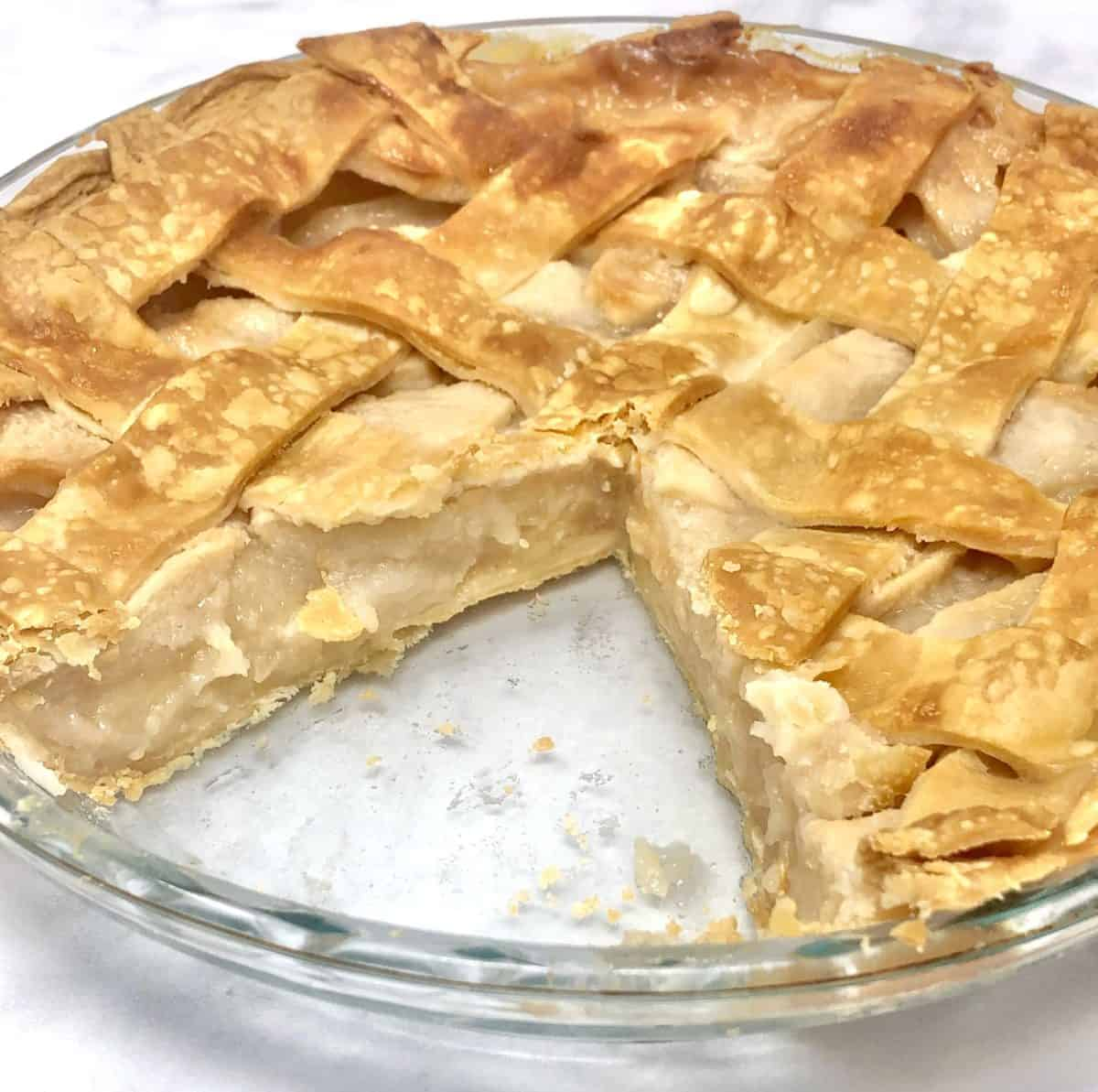 A homemade apple pie with a slice missing from it.