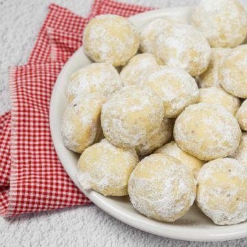 A pile of pecan snowball cookies on a plate.