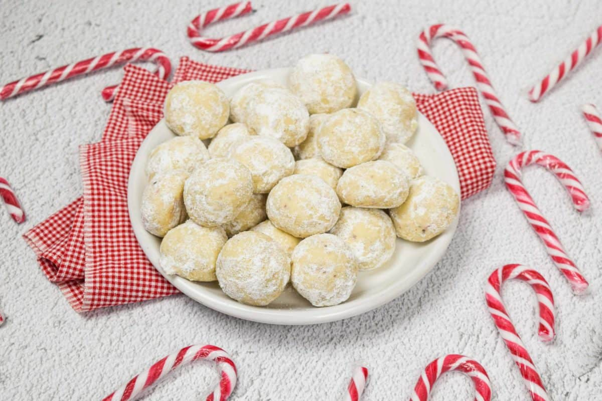 A plate of pecan cookie snowballs with candy canes.