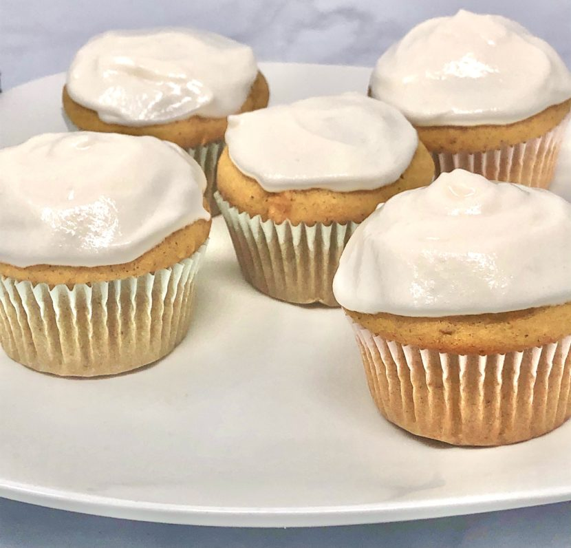 A close up of 5 sweet potato cupcakes on a plate.