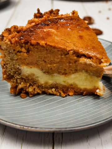 A slice of gingersnap pumpkin cheesecake on a plate with a fork.