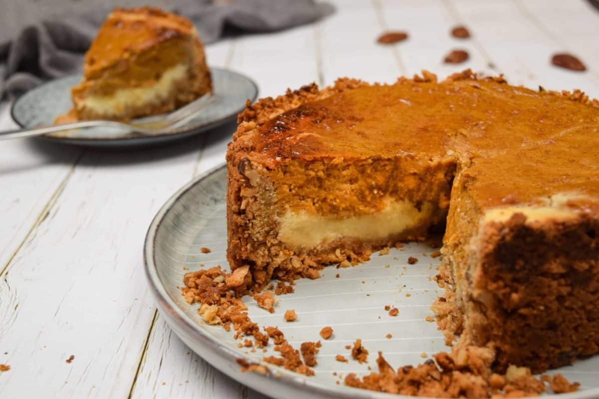 A gingersnap pumpkin cheesecake on a dish with a slice missing.