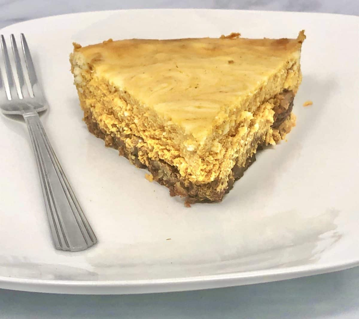 A slice of marble pumpkin cheesecake on a plate with a fork.
