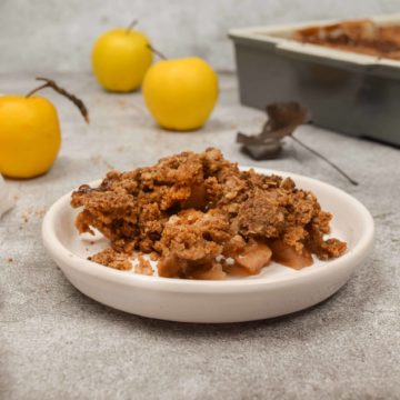 A bowl of old fashioned apple crisp on a table.