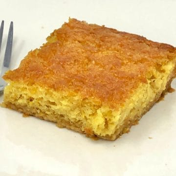 A close up piece of Greek orange pie on a plate with a fork.