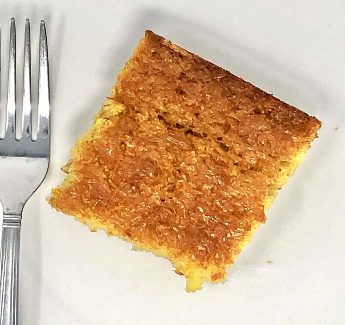 A piece of Greek orange pie on a plate with a fork.