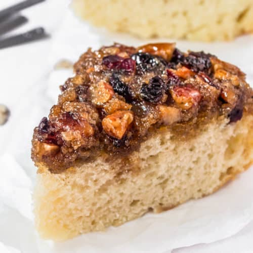 A slice of sour cream cranberry coffee cake on a table.