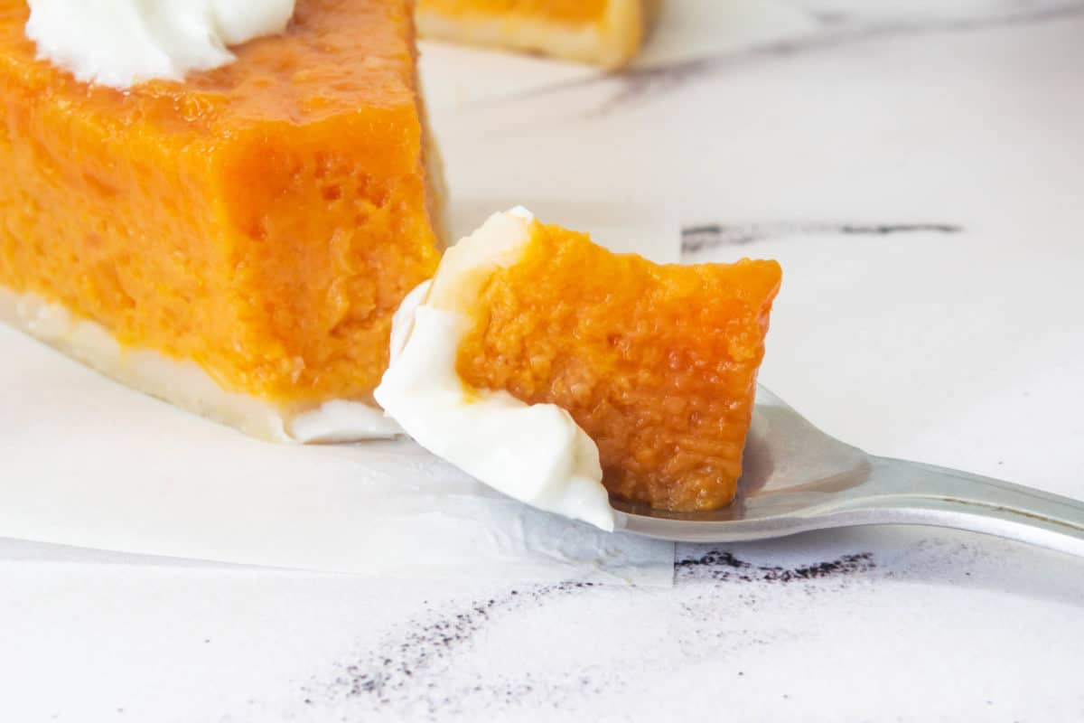 A close up of sweet potato pie on a spoon.