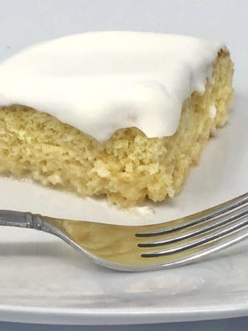 A close up of a piece of shortcut tres leches cake on a plate with a fork.