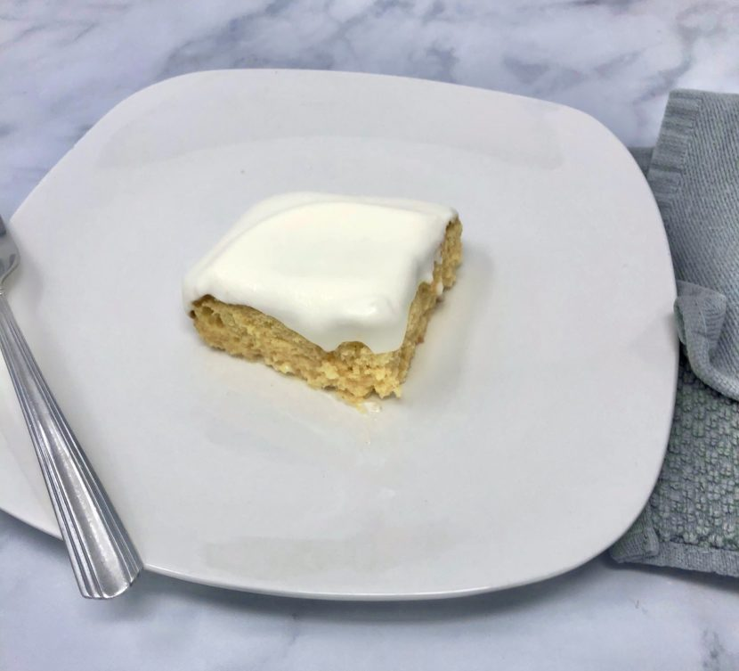 A piece of shortcut tres leches cake on a plate with a fork.