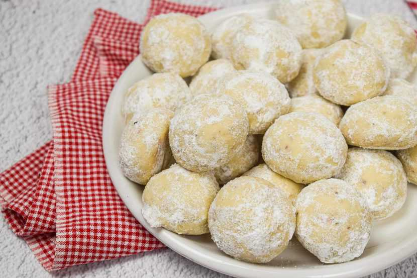 A bowl of snowball cookies with pecans.