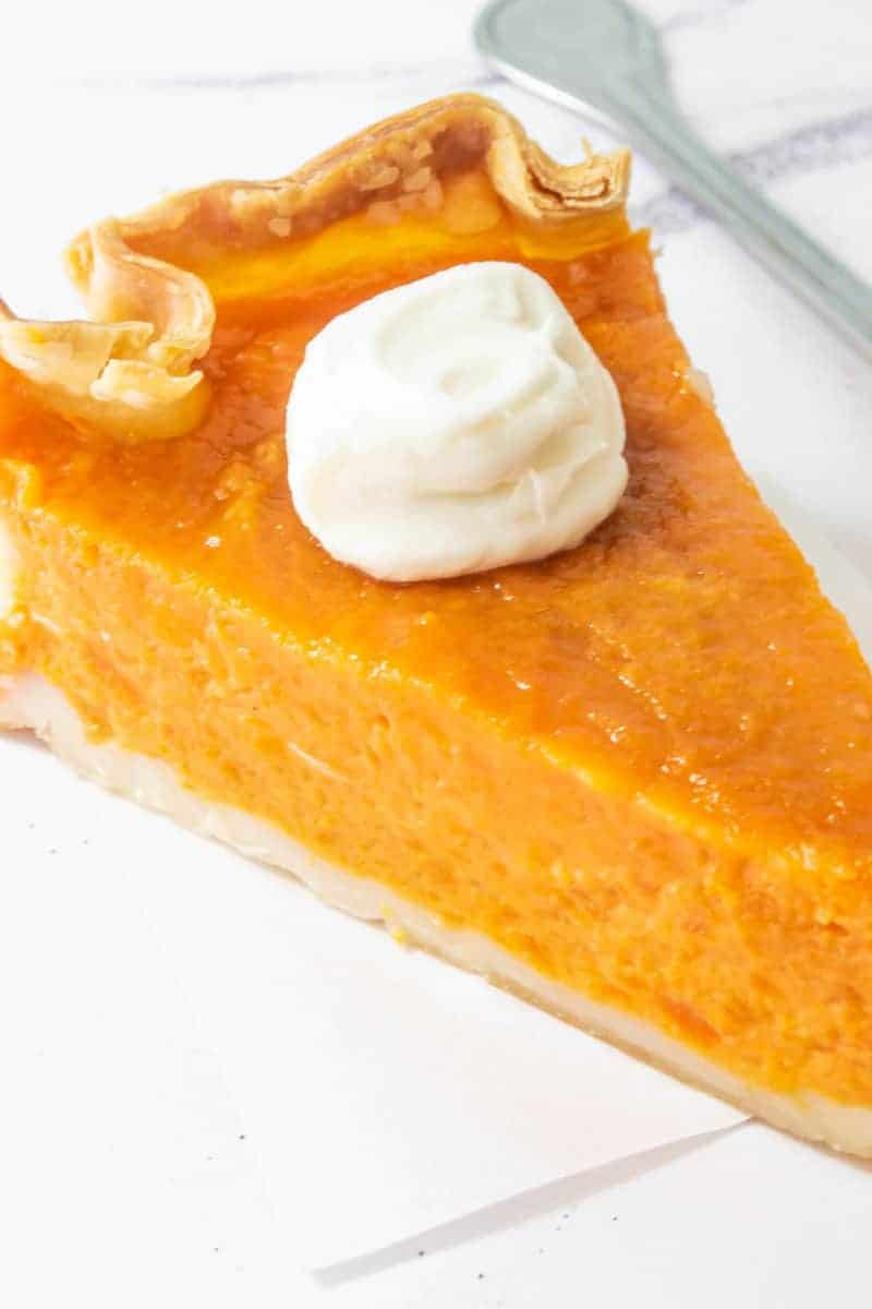 A close up for sweet potato pie with whipped cream on the top of it.