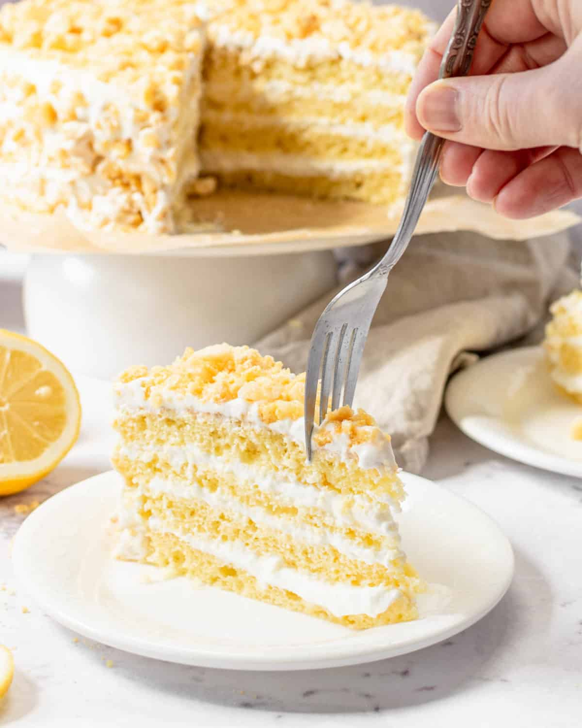 A fork pushing down into a slice of lemon crunch cake.