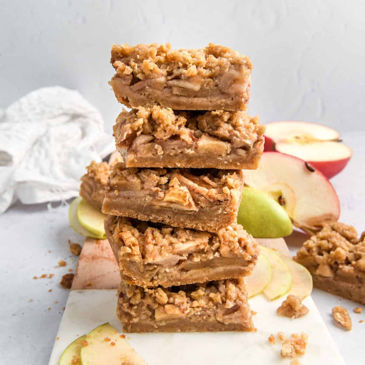 A stack of five bars with fresh apple slices in the background.