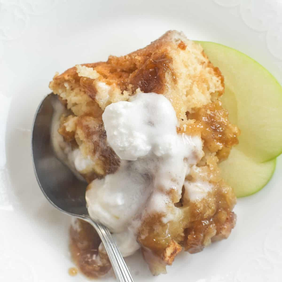 A close up of apple cobbler in a spoon.