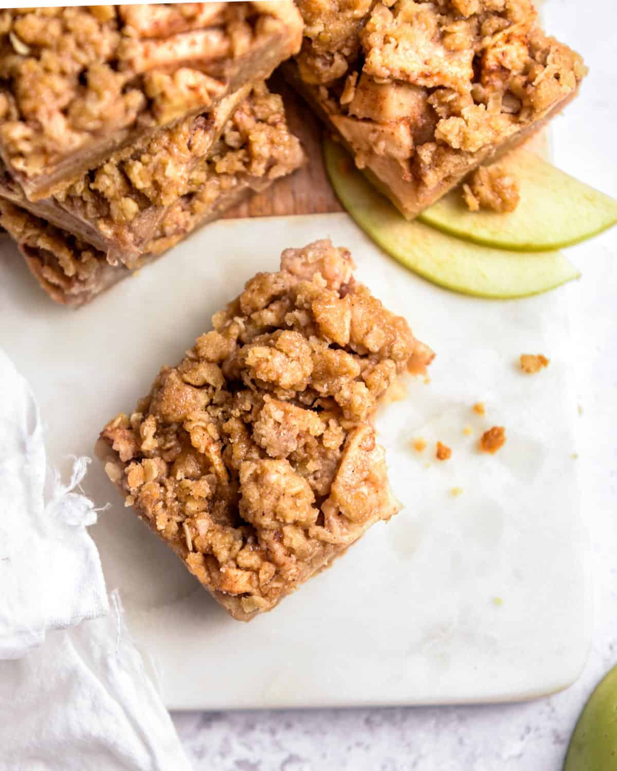 An apple crisp bar with a bite taken out of it and crumbs around it.