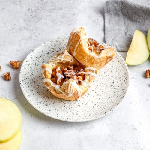 Two apple pie puff pastries on a plate ready to eat.