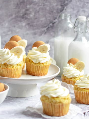 Several banana cream cupcakes on a cake stand.