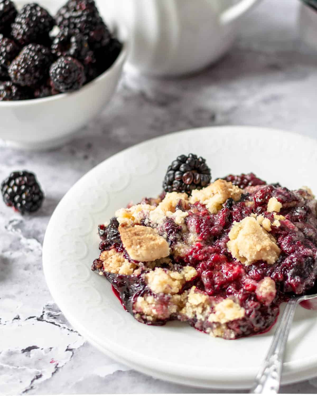 A large scoop of blackberry cobbler on a white plate with a spoon.