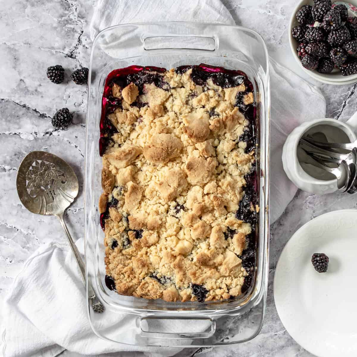 Finished blackberry cobbler dessert in a baking dish with spoons and blackberries.