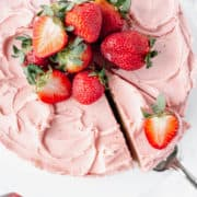 An overhead shot of a strawberry cake topped with fresh strawberries.