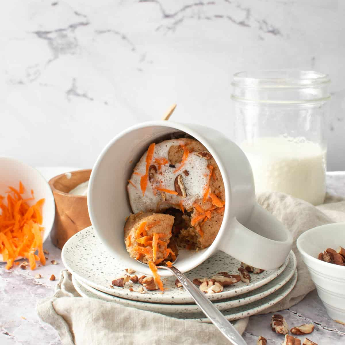 Carrot cake in a mug with a spoon.