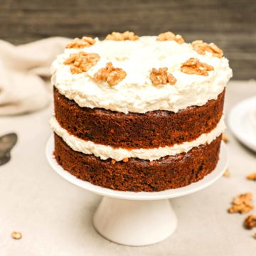 A carrot cake with raisins on a cake stand.