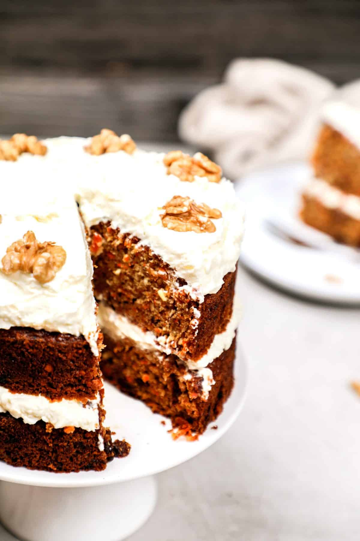 A carrot cake with a slice cut out showing the inside.