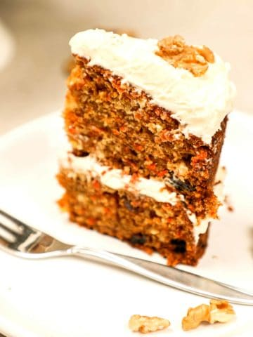 A slice of carrot cake on a plate with a fork.