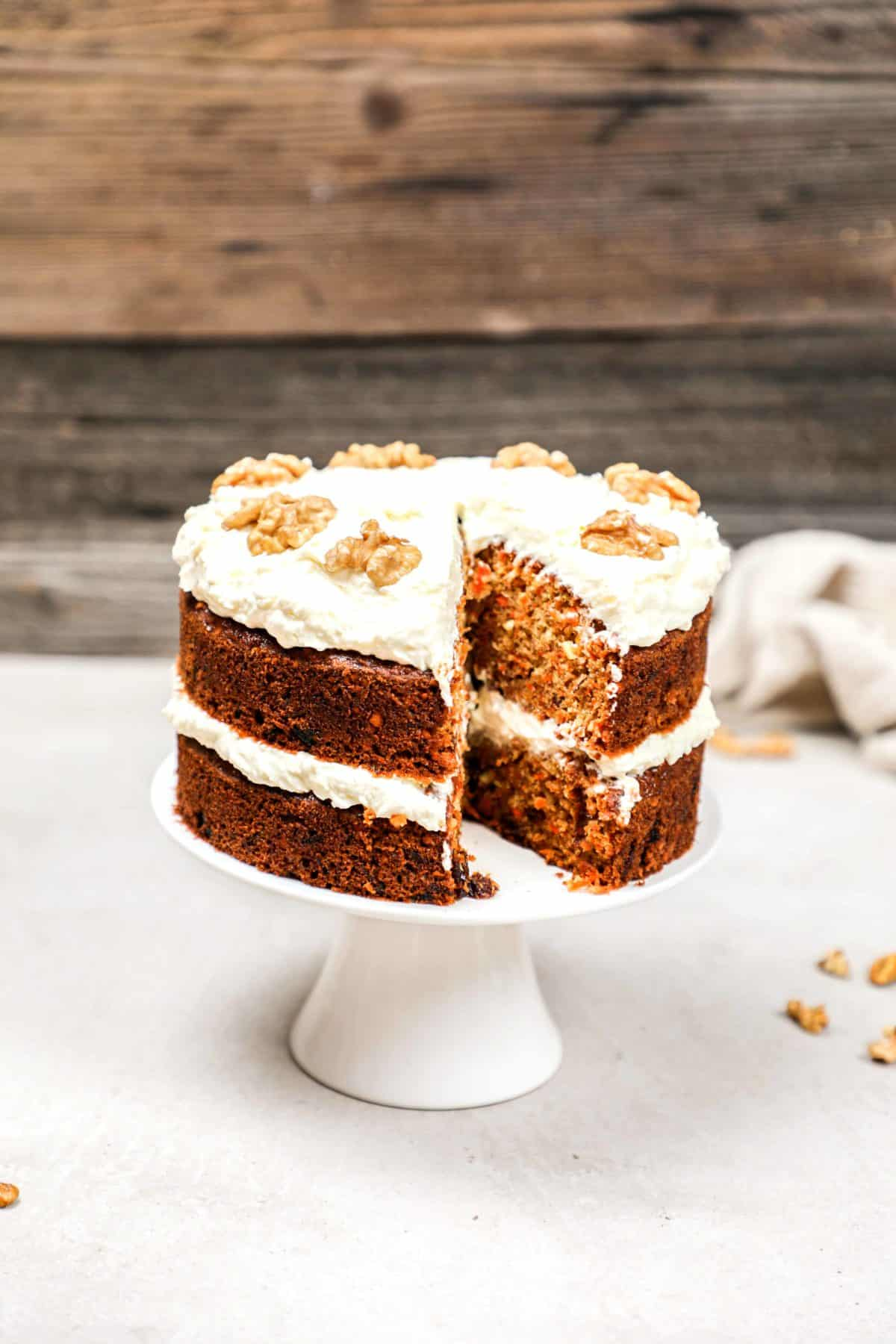 A carrot cake on a cake stand with a slice cut out of it.