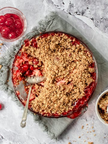 Finished cherry apple crisp in a baking dish on a table.