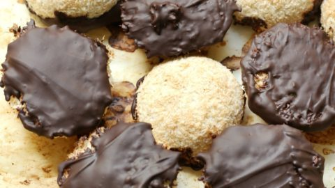Several chocolate-dipped coconut macaroons on a table.