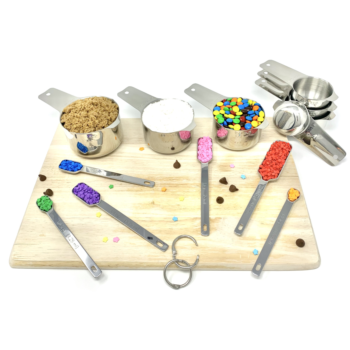The complete measuring set on a cutting board with baking ingredients.