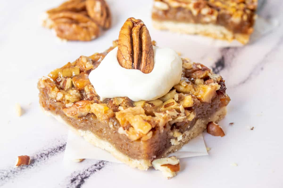 A pecan pie bar up close topped with whipped cream.