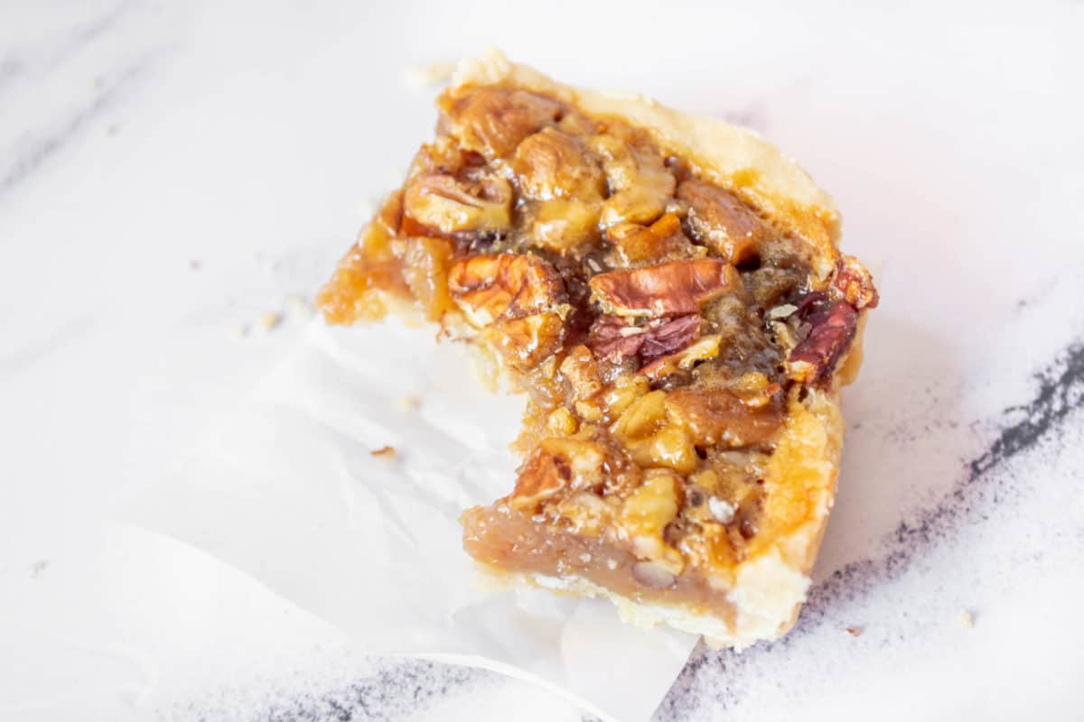 A classic pecan pie bar with a bite taken out of it.