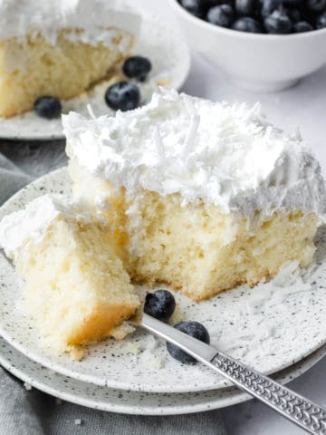 A bite of coconut poke cake on a plate with a fork.