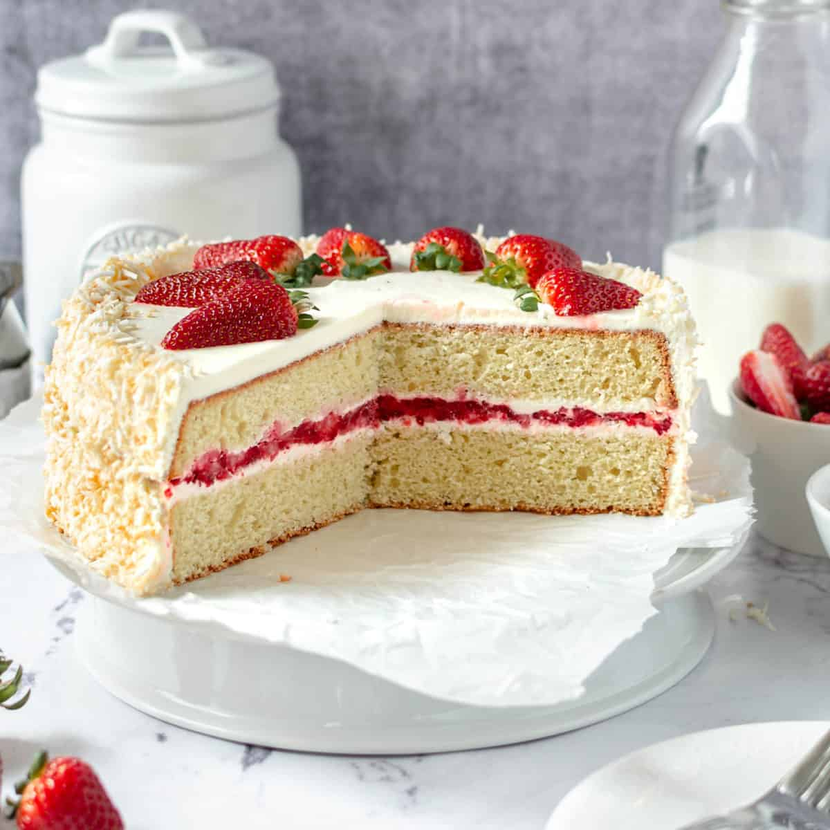 A coconut strawberry cake with some slices cut out of it.