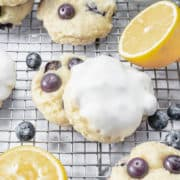 Freshly baked lemon blueberry cookies on a cooling rack.