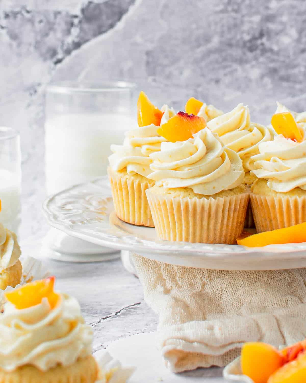 Several peach cupcakes on a cake stand.